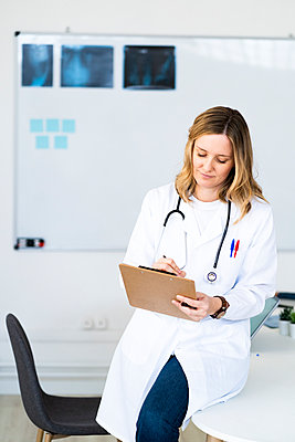 Female doctor writing on clipboard while sitting on desk at medical clinic - p300m2265467 by Giorgio Fochesato