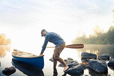 Man pushing canoe into still lake - p429m1450723 by Hugh Whitaker