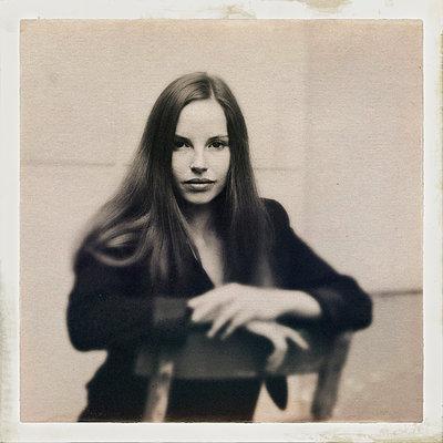 Langhaarige Frau auf einem Stuhl, Porträt - p586m1109999 von Kniel Synnatzschke