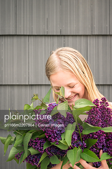 Young Blonde Girl Holding Bunch of Lilacs and Smiling - p1166m2207864 by Cavan Images