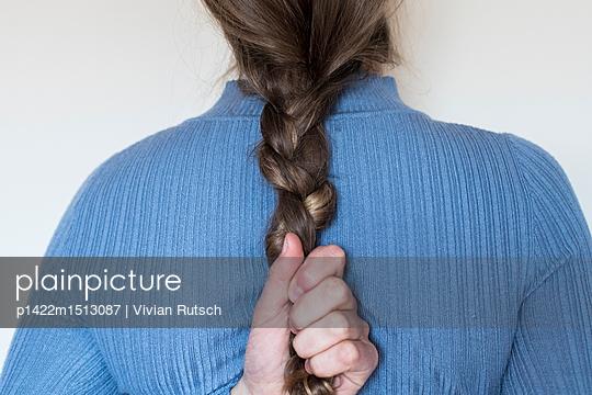 Junge Frau greift nach ihrem Zopf - p1422m1513087 von Vivian Rutsch