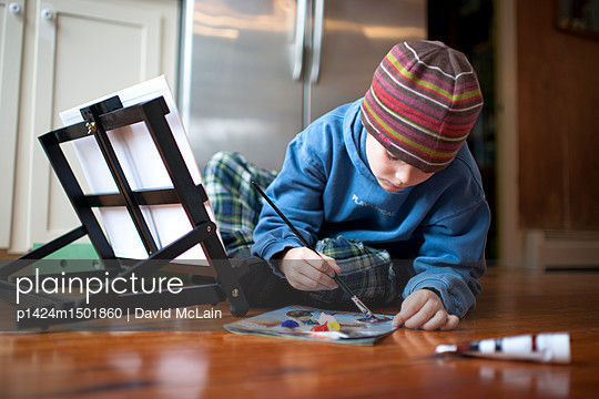 A young boy paints  at his home  in North Yarmouth, Maine. - p1424m1501860 by David McLain