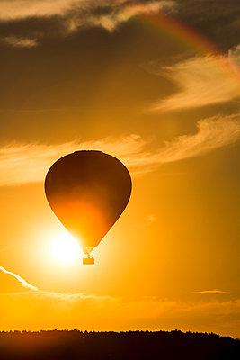 A hot air ballon flies past the setting sun - p1057m931349 by Stephen Shepherd