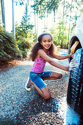 Portrait of girl kneeling while washing car in driveway - p1166m1225980 by Cavan Images