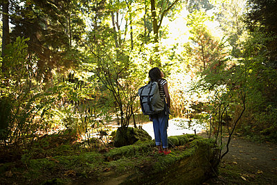 Curious girl with backpack exploring in woods, looking up at trees in wonder - p1192m1511860 by Hero Images