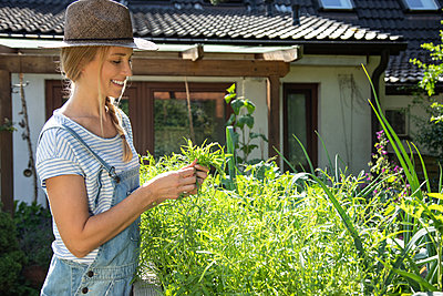 Woman working in her garden - p1678m2258823 by vey Fotoproduction