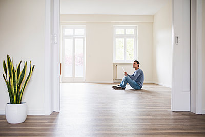 Young man in new home sitting on floor with tablet - p300m1459739 by Uwe Umstätter