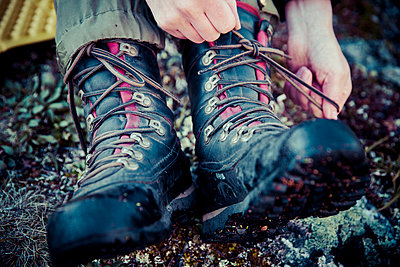 Low section of female hiker tying laces of hiking boots - p426m844647f by Katja Kircher