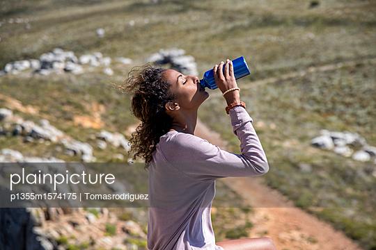 Junge Frau trinkt Wasser auf einer Bergwanderung - p1355m1574175 von Tomasrodriguez