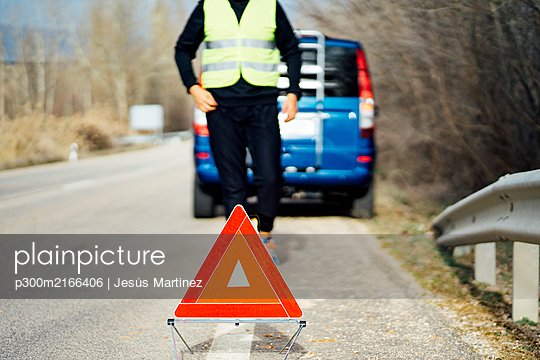 Man putting warning triangle on country road by van breakdown - p300m2166406 by Jesús Martinez