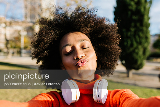 Young woman with eyes closed puckering while taking selfie at park - p300m2257503 by Xavier Lorenzo