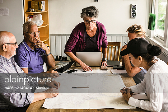 Female instructor explaining senior men and woman over map at table during navigation course - p426m2149414 by Maskot