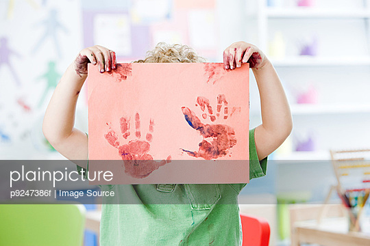 Boy holding up painted hand print - p9247386f by Image Source