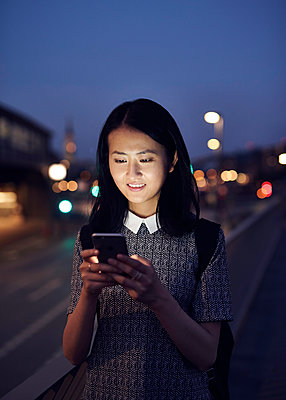 Asiatin mit Smartphone in der Dämmerung - p1124m1169919 von Willing-Holtz