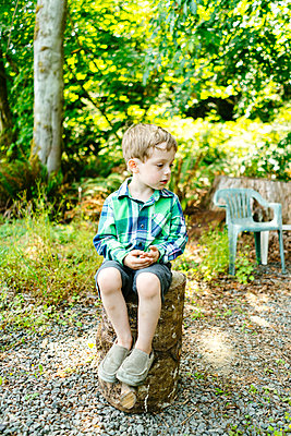 Straight on view of a young boy sitting on a log stool - p1166m2131381 by Cavan Images