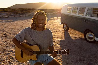 Happy young man playing guitar near camper van at beach - p1315m2117874 by Wavebreak