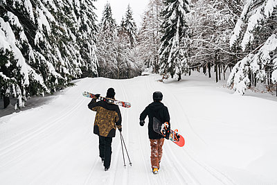 Italy, Modena, Cimone, rear view of couple with skiers and snowboard walking in winter forest - p300m2029370 von Juri Pozzi
