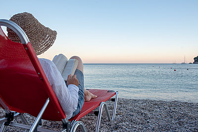 Greece, Parga, woman on deckchair reading book on the beach at sunset - p300m2043050 by Petra Silie