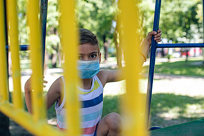 Boy wearing face mask while playing in playground during COVID-19 - p300m2206992 by Mosuno Media