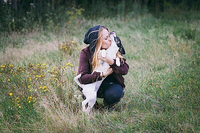 Woman kissing dog while crouching in grassy field - p301m1534953 by Isabella Ståhl