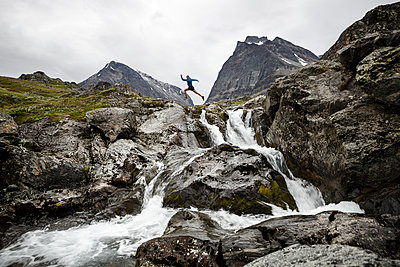 Person jumping over mountain river - p312m1522004 by Michael Jonsson