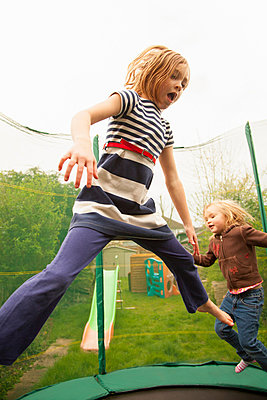 Girls jumping on trampoline - p429m859997f by Robert Christopher