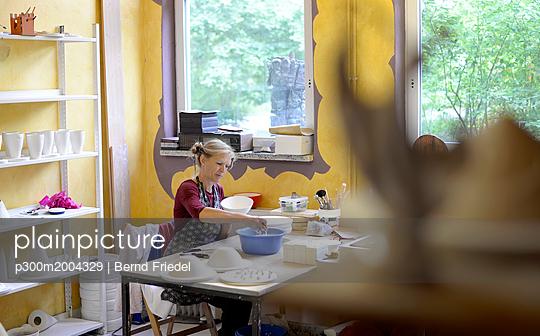 Woman working in porcelain workshop - p300m2004329 von Bernd Friedel