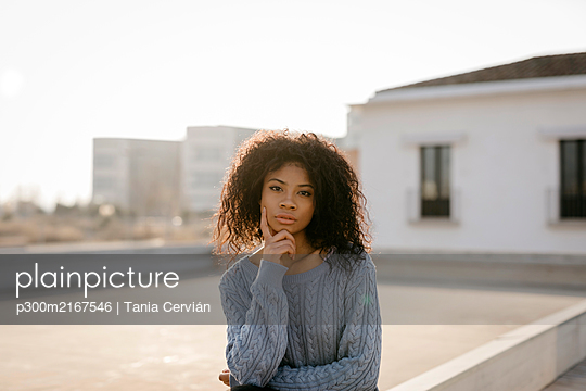 Portrait of a beautiful young woman on a rooftop at sunset - p300m2167546 von Tania Cervián
