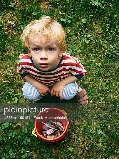 Kleiner Junge sammelt Steine und Federn - p358m1160181 von Frank Muckenheim