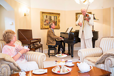 Tea party with music performance in background - p1026m1164198 by Patrick Frost