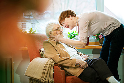 Adult daughter greeting her mother with Alzheimer's disease in her room at retirement home - p300m1120747f by Jan Tepass