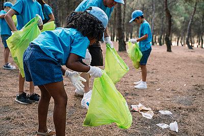 Group of volunteering children collecting garbage in a park - p300m2131994 von Jose Luis CARRASCOSA