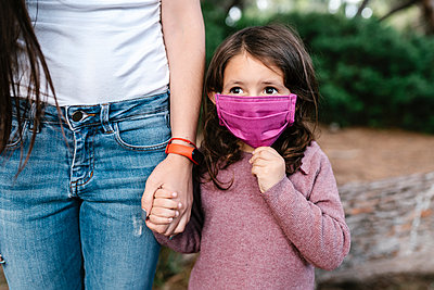 Daughter wearing protective mask and holding hand of her mother - p300m2202566 by Ezequiel Giménez