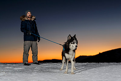 Mature man standing with dog in snow at night - p429m1408274 by Quim Roser