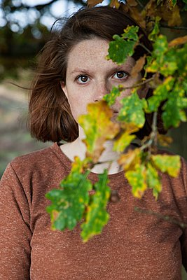Woman in the woods hiding behind a branch  - p896m1490458 by Rutger van der Bent