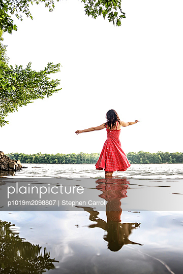 Woman standing with arms outstretched in river - p1019m2098807 by Stephen Carroll