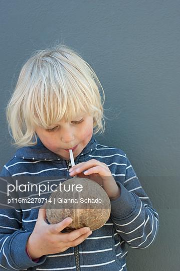 Child drinking coconut milk - p116m2278714 by Gianna Schade