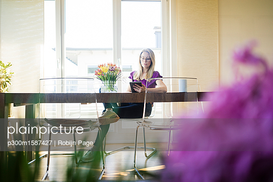 Businesswoman sitting at meeting table using tablet - p300m1587427 von Robijn Page