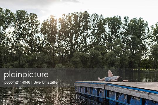 plainpicture - plainpicture p300m2114946 - Relaxed woman lying on jett... - DEEPOL by plainpicture/Uwe Umstätter