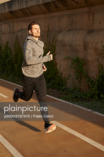Man running on a road in sunlight - p300m2167416 by Pablo Calvo