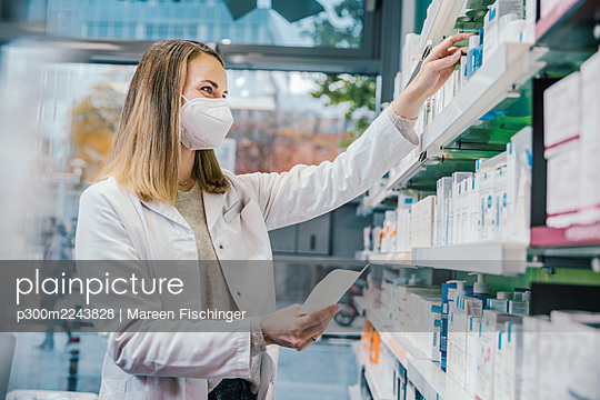 Female pharmacist wearing protective face mask while working in chemist shop - p300m2243828 by Mareen Fischinger