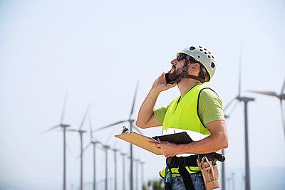 Energy engineer using smart phone at wind farm - p1166m1164522 by Cavan Images