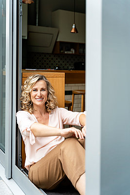 Happy female entrepreneur sitting at doorway of office cafeteria - p300m2241087 by Peter Scholl