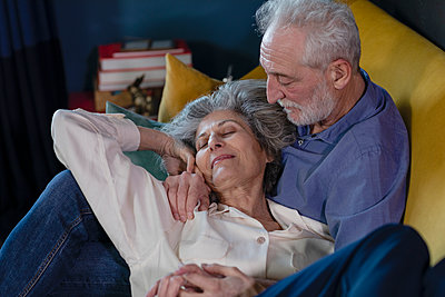Smiling woman resting on senior man lap at home - p300m2265123 by Emma Innocenti