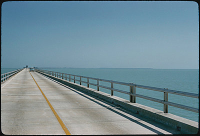 Long bridge over water with oncoming car in distance - p3720630 by James Godman