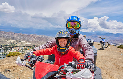Mother and son on top of mountain, using quad bike, La Paz, Bolivia, South America - p429m1557396 by Stephen Lux