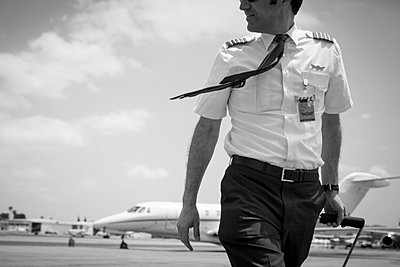 Black and white image of male private jet pilot arriving at airport - p924m1081710f by Raphye Alexius