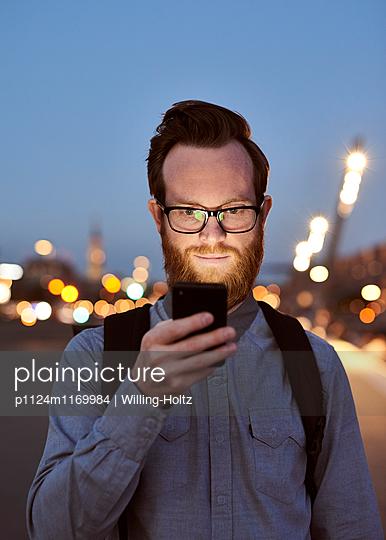 Mann mit Smartphone in der Dämmerung - p1124m1169984 von Willing-Holtz