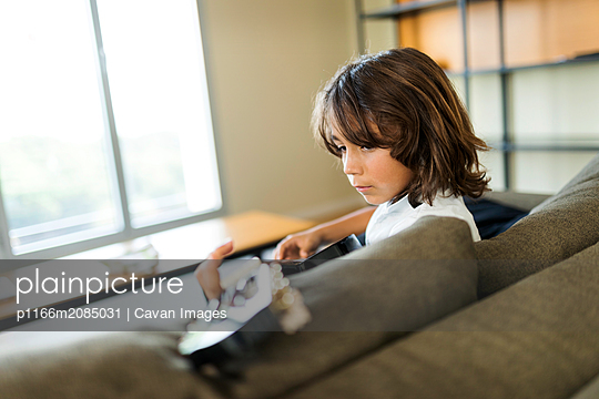young boy playing guitar sitting on the sofa at home - p1166m2085031 by Cavan Images