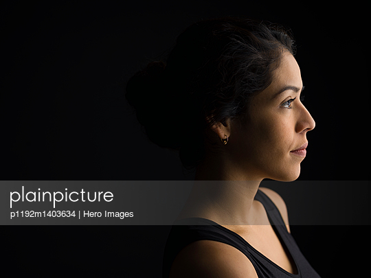 Profile portrait serious, pensive Latina woman looking away against black background - p1192m1403634 by Hero Images
